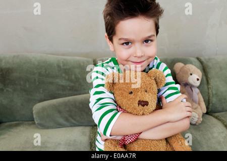 Portrait of young boy on sofa hugging teddy - Stock Photo