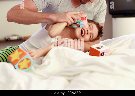 Father and young son playing with building blocks on bed - Stock Photo
