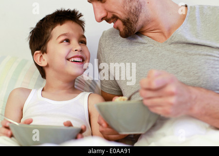 Father and young son having breakfast in bed - Stock Photo