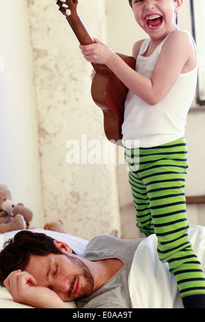 Son playing guitar whilst his father sleeps - Stock Photo