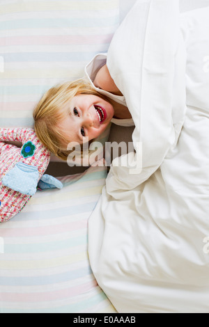 Portrait of young girl lying in bed with toy elephant - Stock Photo