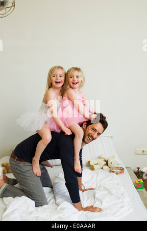 Portrait of mid adult father giving two young daughters a piggy back - Stock Photo