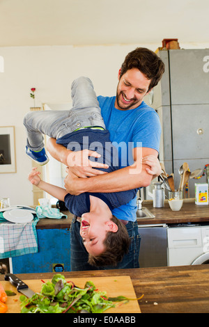 Father holding young son upside down in kitchen - Stock Photo