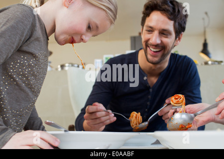 Mid adult man and family eating a spaghetti meal - Stock Photo