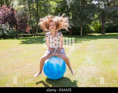 Girl jumping on space hopper - Stock Photo