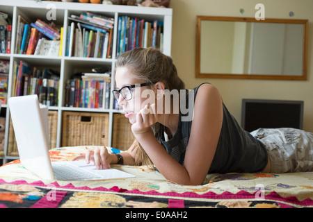 Teenage girl lying on front using laptop - Stock Photo