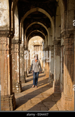 Woman walking in colonnade at Jami Masjid (Grand Mosque), Champaner-Pavagadh Archaeological Park, Gujarat, India - Stock Photo