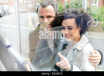 Couple window shopping, young woman pointing - Stock Photo