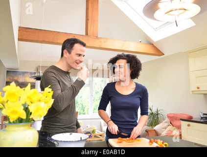 Couple in kitchen tasting and slicing peppers - Stock Photo