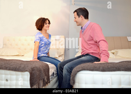 Couple sitting on beds in furniture shop showroom - Stock Photo