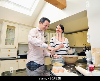 Mid adult couple baking in kitchen - Stock Photo