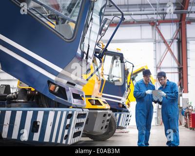 Engineers check details on digital tablet in truck repair factory - Stock Photo