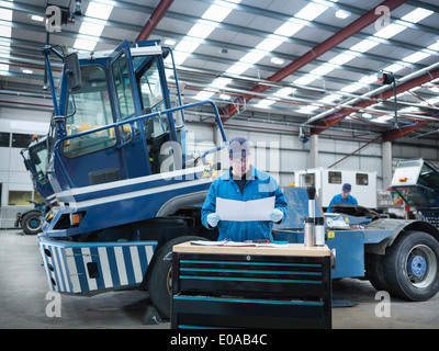 Engineer working from plans in truck repair factory - Stock Photo