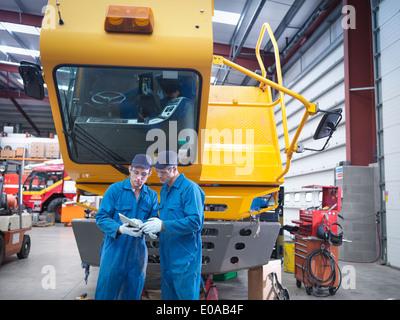 Engineers use digital tablet in truck repair factory - Stock Photo