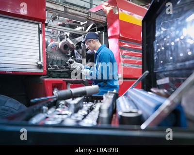 Engineer working on engine in truck repair factory - Stock Photo