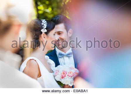 Mid adult bride and groom surrounded by wedding guests - Stock Photo