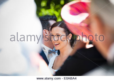 Mid adult bride and groom surrounded by guests - Stock Photo