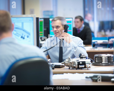 Engineer using telephone at desk in office - Stock Photo
