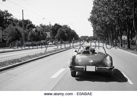 B&W image of just married couple kissing in car on highway - Stock Photo