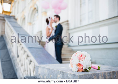 Mid adult bride and groom kissing on stairway - Stock Photo
