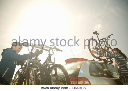 Mother and son stacking bikes on bike rack - Stock Photo