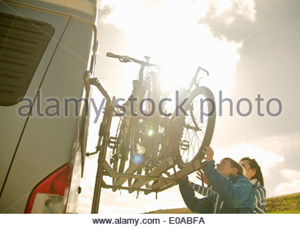Mother and son stacking bikes on back of camper van - Stock Photo