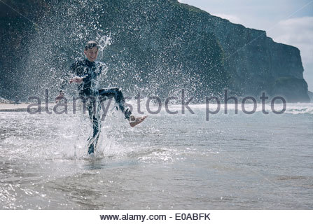 Boy wearing wetsuit, splashing in sea - Stock Photo