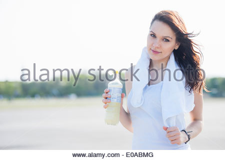 Young woman with towel around neck, with bottle of water - Stock Photo
