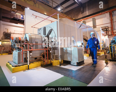 Engineer in generator room of power station - Stock Photo