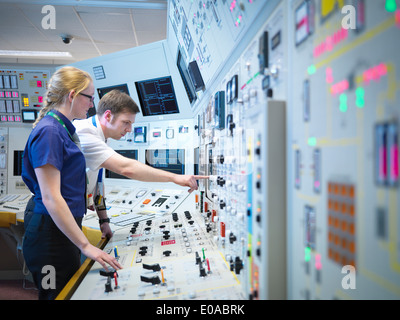 Female operator and trainee in nuclear power station control room simulator - Stock Photo