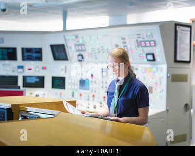 Female operator reading notes in nuclear power station control room simulator - Stock Photo