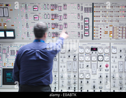 Operator adjusting controls in nuclear power station control room simulator - Stock Photo