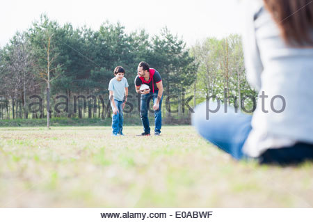 Boy practicing rugby with parents in park - Stock Photo
