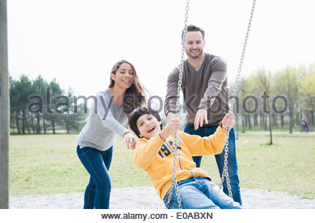 Parents pushing son on park swing - Stock Photo