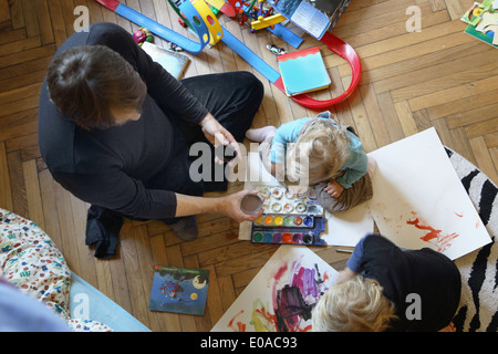 Father and sons painting on floor - Stock Photo
