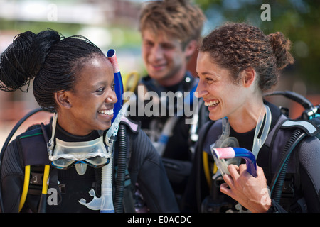 Three young adult scuba divers preparing for pool practice - Stock Photo