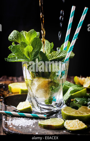 Glass of mojito cocktail with pouring rum and soda, fresh mint, limes and ice cubes over black background. - Stock Photo