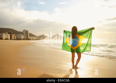 Woman holding Brazilian flag on Copacabana Beach, Rio, Brazil - Stock Photo