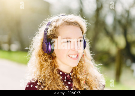 Portrait of teenage girl listening to headphones - Stock Photo