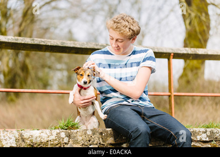 Teenage boy sitting on footbridge with his jack russell dog - Stock Photo