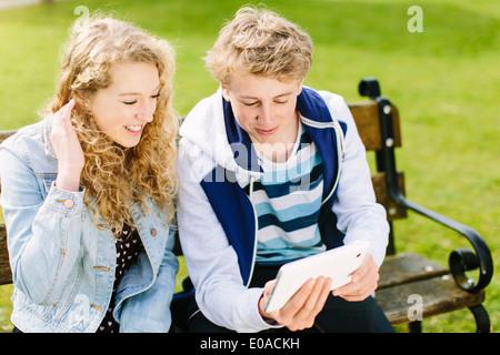 Teenage siblings looking at digital tablet on bench - Stock Photo
