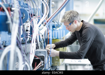 Mid adult male technician maintaining cables in engineering plant - Stock Photo