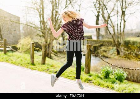 Teenage girl jumping mid air on rural road - Stock Photo