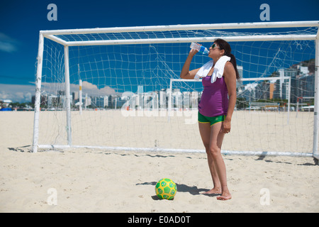 Mature woman and soccer ball on Copacabana beach, Rio De Janeiro, Brazil - Stock Photo