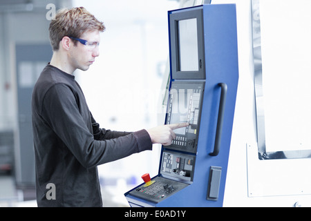 Mid adult male technician maintaining machines in engineering plant - Stock Photo