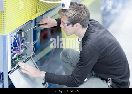 Mid adult male technician maintaining equipment in engineering plant - Stock Photo