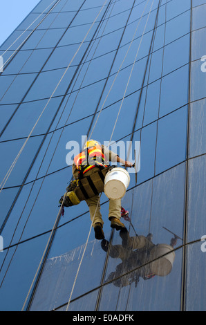 Window cleaner works on  high rise building - Stock Photo