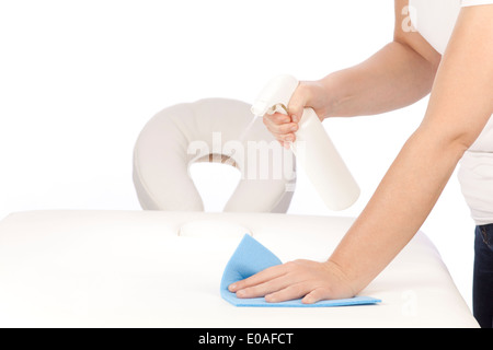Disinfecting a massage table - Stock Photo