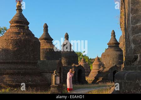 Nun praying at Andaw-thein Temple, Mrauk-U, Rakhine State, Myanmar - Stock Photo