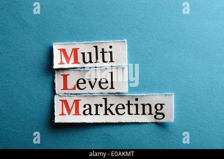 mlm - multi level marketing on blue paper - Stock Photo